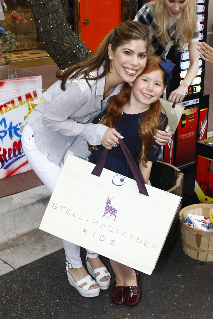 A mother-daughter duo collect their Stella McCartney Kids winnings after participating in carnival games.