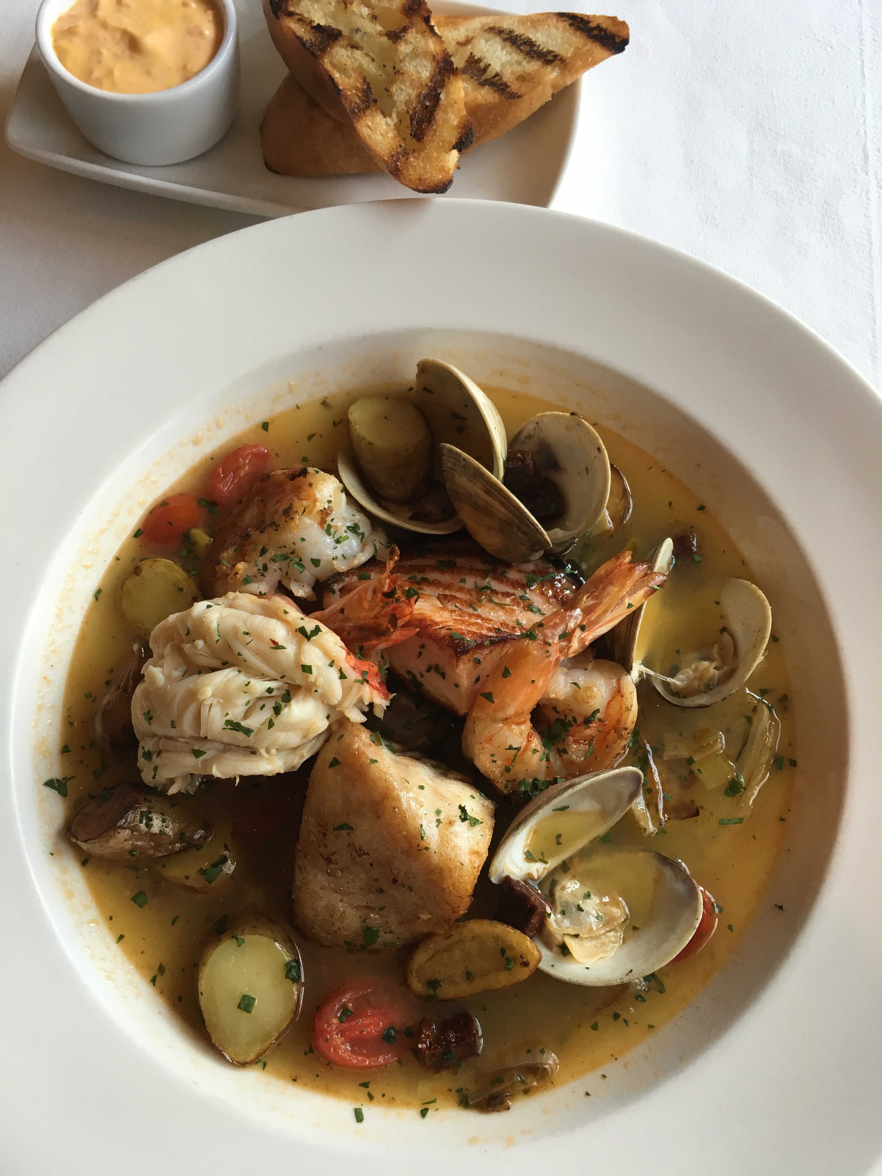 Bouillabaisse prepared with Alaskan Halibut, Bay of Fundy Salmon, White Shrimp, Littleneck Clams and a Lobster Tail.